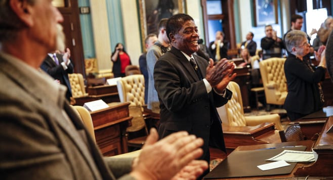 Henry Hatter, a Michigan Electoral College representative, applauds after turning in his signed vote for President-elect Donald Trump at the State Capitol in Lansing, Michigan on Dec. 19.