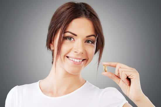 Smiling Brunette Holding a Yellow Capsule