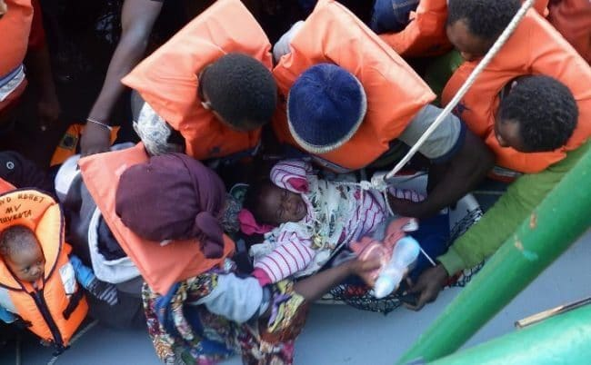Image result for A baby being taken on to MSF's Bourbon Argos ship from a boat carrying 130 migrants and refugees